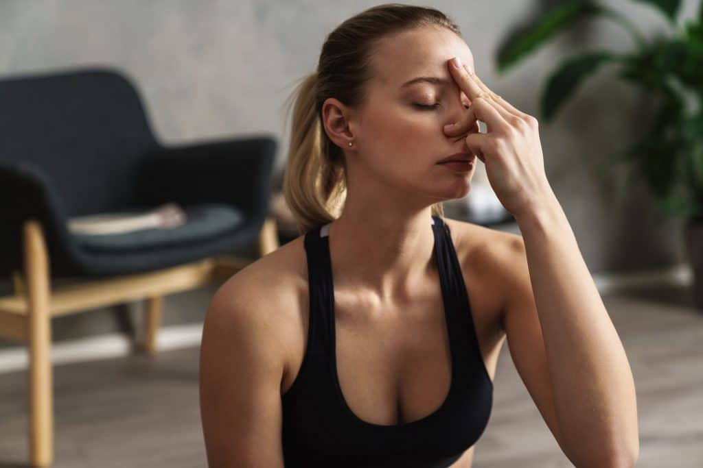 Attractive young woman practicing yogic breathing technique