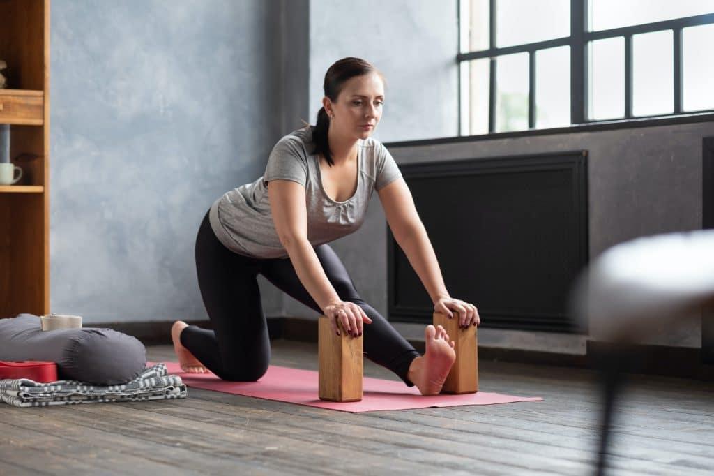 woman doing stretching exercise using props, block, Ardha Hanumanasana